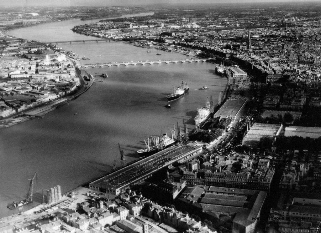 Vue aérienne du port de Bordeaux dans les années 1940 avec les quais, les hangars et le pont de pierre. Crédit photo - Archives Sud Ouest